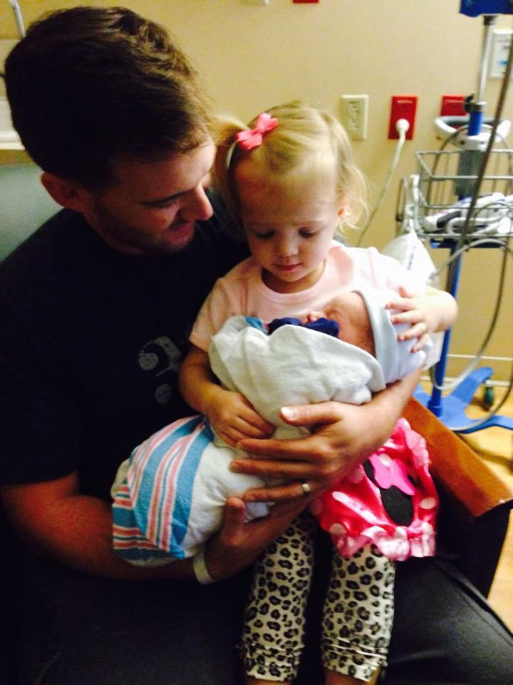 Dad holds big sister Audrey as she meets her new little brother